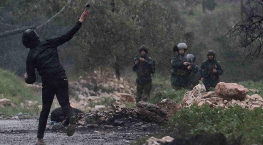 شاب يواجه قوات الاجتلال بالحجارة